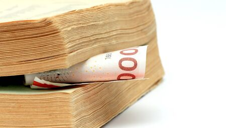 cost of education: 1000 danish kroner between pages of an old book. Education concept. Stock Photo