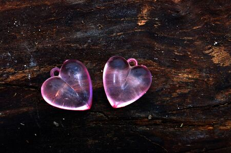 plastic heart: picture of a pink plastic heart on tree bark background. valentines day celebration concept.