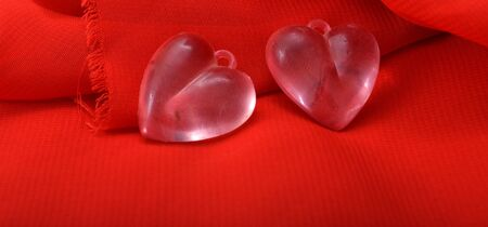 plastic heart: picture of a pink plastic heart on red canvas background. valentines day celebration concept. Stock Photo