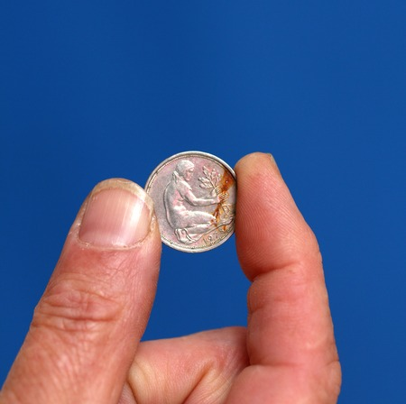 numismatic: picture of a Fingers hold old coin from Austria