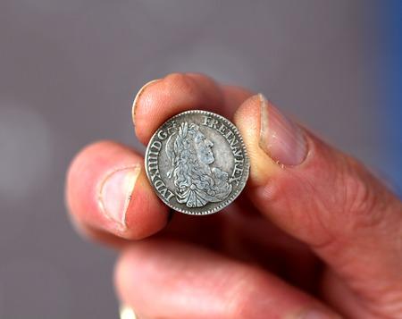 monedas antiguas: dibujo de unos dedos mantenga la moneda antigua de Francia, moneda de plata del rey Luis XIV