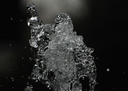 foto di una goccia d'acqua levitare in aria nel buio. fly spruzzi d'acqua in aria. Parte delle gocce è a fuoco, una parte - fuori dal fuoco.
