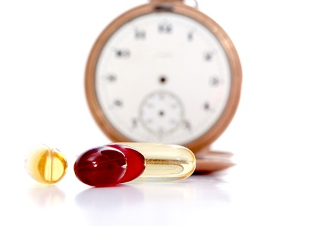 cod oil: picture of a Cod liver oil omega 3 and krill oil gel capsules in front of vintage pocket clock Stock Photo