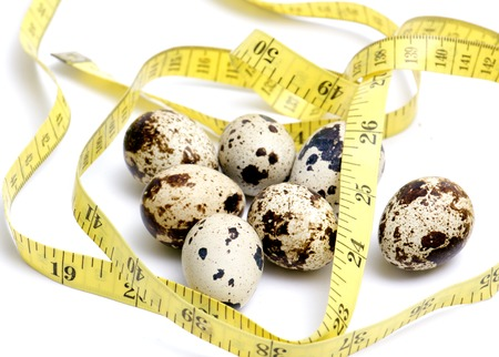 japanese quail eggs and tape measure ,food , health and diet concept Stock Photo