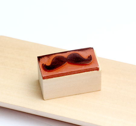 mococa: picture of a moustaches rubber stamp. Movember mens health awareness concept. Stock Photo