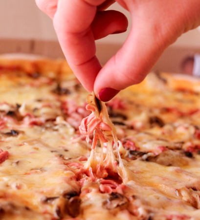 picking fingers: Fresh pizza in macro view.woman fingers picking up piece,