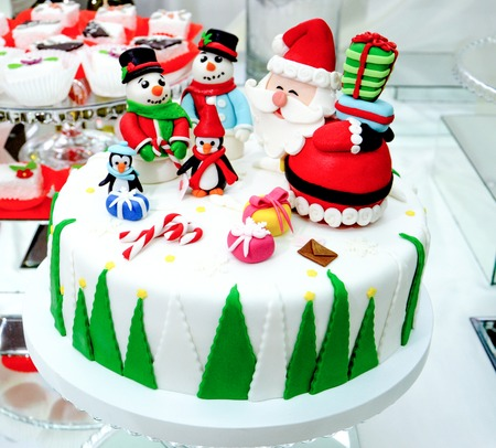 picture of a homemade christmas cake decorated with sweet gihurines of santa,snowmen, penguins