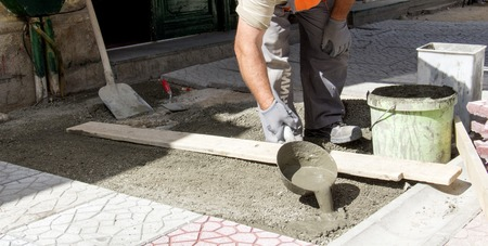 simetry: picture of a Worker pouring cement for pavement instalation