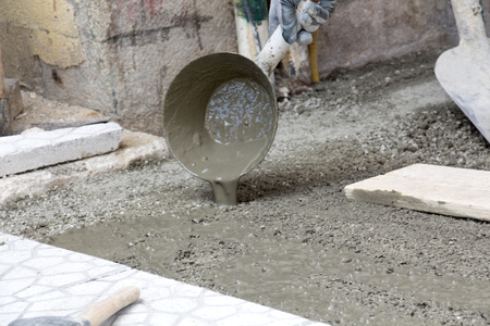 simetry: picture of a Worker pouring cement for pavement installation Stock Photo