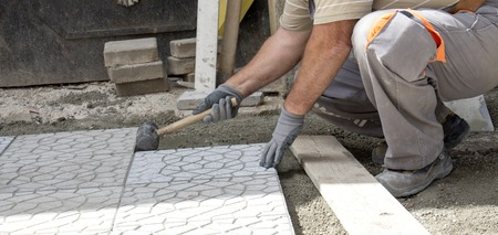 pavers: picture of a Worker tapping pavers into place with rubber mallet. Stock Photo