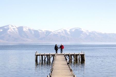 mujer mirando el horizonte: picture of an adult couple romance on a pier of lake prespa,macedonia