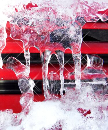 picture of a shiny clear ice icicles hang on a red car surface Stock Photo