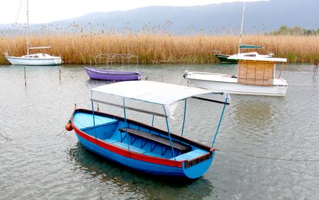 trawler net: tourist and fisherman boats on lake ohrid in macedonia,