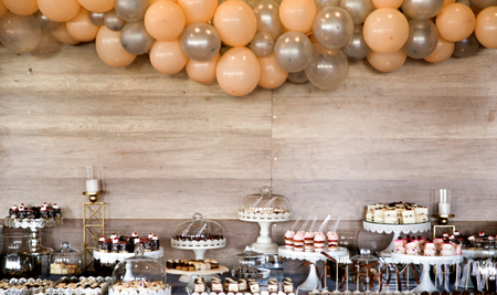 image of an assorted sweets on party table. wood background with baloons, Standard-Bild