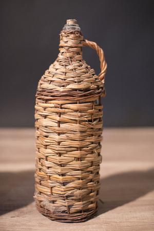 rakia: image of a glass bottle for rakia protected by wood mesh Stock Photo