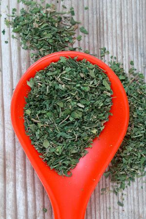 dried organic parsley in a plastic spoon , image of a