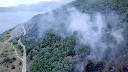 smoke of bush fire near village houses in macedonia