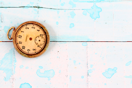 image of a vintage pocket clock on a blue painted wood suraface Stock Photo