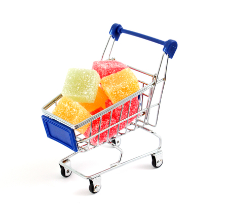bakground: Colored Sweet.Jellies on a shopping cart, white bakground, image of Stock Photo