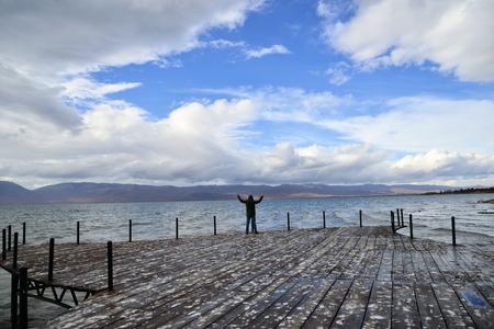 celebrating freedom. Positive human emotions, feeling life perception ,success, peace of mind concept. man on a a pier. lake prespa,macedonia Stock Photo