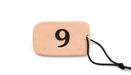 number on , brown ceramic plate ,necklace, on white background,image of a Foto de archivo