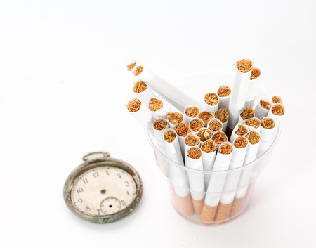 cigarettes in a disposable cup and vintage clock on white background,image