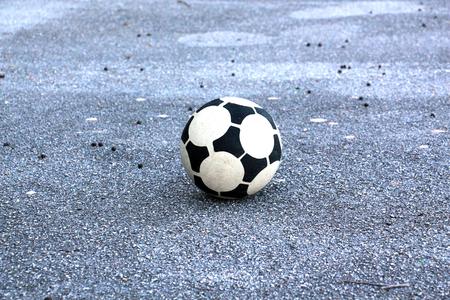soccer ball on an old asphalt road, image of a