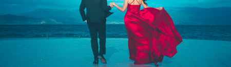unrecognizable groom and bride in red satin dress