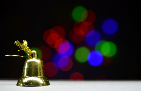 gold colored christmas bell on a bokeh background Stock Photo