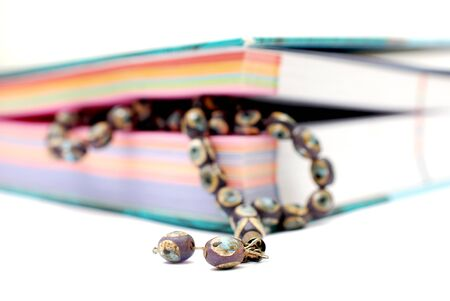 old prayer beads between colorful book pages