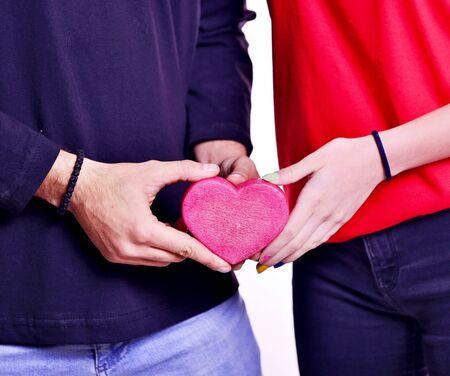 male and female handing piece of heart shaped object. 版權商用圖片