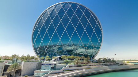 Circular skyscraper Aldar Headquarters Building timelapse hyperlapse in Abu Dhabi, UAE. View from bridge. It is the first circular building of its kind in the Middle East.