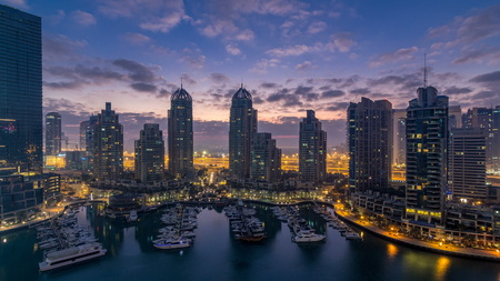 Aerial view of modern skyscrapers night to day transition timelapse before sunrise in Dubai Marina with yachts in Dubai, UAE. Illuminated towers early morning