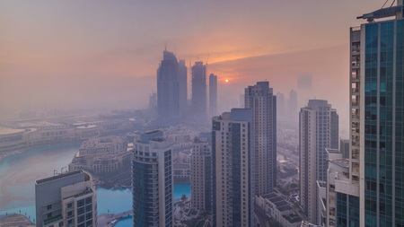 Foggy morning sunrise in downtown of Dubai timelapse. Futuristic view of the city skyscrapers covered in mist. Aerial view from rooftop with modern towers. Dubai, UAE