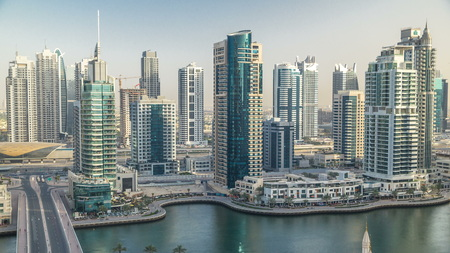 Amazing colorful dubai marina skyline during sunset timelapse. Great perspective of multiple tallest skyscrapers of the world with yachts and boats. Sunlight over buildings. United Arab Emirates. Sajtókép