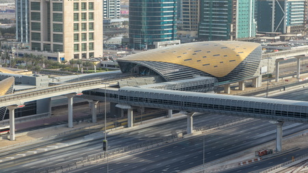 Aerial view of Metro station near Jumeirah lakes towers skyscrapers timelapse with traffic on sheikh zayed road. Bus station near exit. Sunset time with long shadows and reflections on a glass