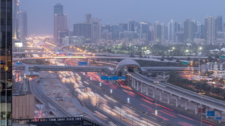 Aerial view of Jumeirah lakes towers skyscrapers and Al Barsha district day to night transition timelapse with traffic on sheikh zayed road and metro line.