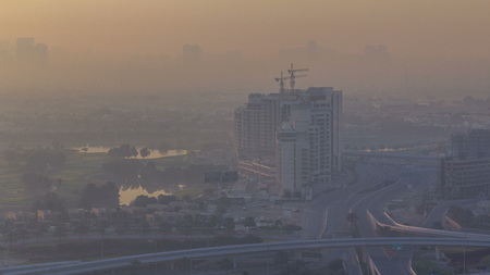 Aerial view of a road intersection near golf course in a big city at sunrise timelapse. Urban landscape of Dubai Marina district in UAE with cars and skyscrapers. Archivio Fotografico