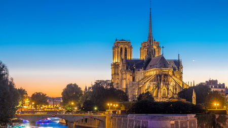 Rear view of illuminated Notre Dame De Paris cathedral day to night transition timelapse after sunset. View from Tournelle bridge. Orange sky in background. Paris, France, Europe.