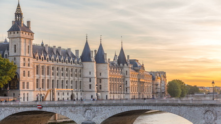 Dramatic sunset over river Seine and Conciergerie timelapse in Paris, France, with boats and Pont Neuf. Colourful travel background. Romantic cityscape.