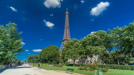 Eiffel Tower from Siene river waterfront in Paris timelapse hyperlapse, France. Blue cloudy sky at summer day with green trees and people walking around