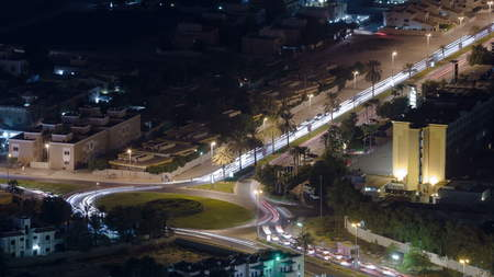 Cityscape of Ajman with traffic on road from rooftop after sunset with lights timelapse. Ajman is the capital of the emirate of Ajman in the United Arab Emirates. 4K