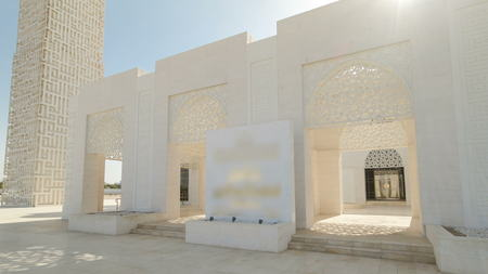 Entrance to White mosque in Ajman timelapse hyperlapse with sun, United Arab Emirates Stock Photo