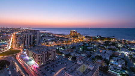 Citiscape of Ajman and Sharjah day to night timelapse from top with Gulf and buildings 4K
