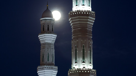 Illuminated Minarets of The Hazrat Sultan Mosque in Astana timelapse at night with full moon passing between, Kazakhstan Stockfoto