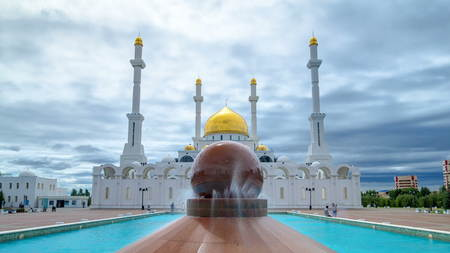 Nur Astana mosque exterior with the fountain at the foreground timelapse hyperlapse in Astana, Kazakhstan. This mosque is the second largest in Kazakhstan. Cloudy sky at summer day
