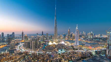 Dubai Downtown day to night transition timelapse with Burj Khalifa and other towers view from the top before new year celebration in Dubai, United Arab Emirates. Lights turning on.