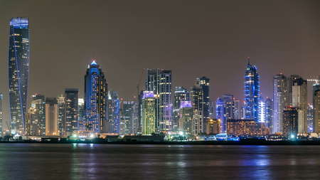 Dubai Marina skyline with JBR night timelapse as seen from Palm Jumeirah in Dubai, UAE. This part of Dubai has more skyscrapers over 50 stories 写真素材