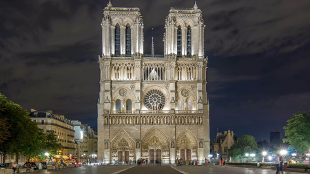 Night View of illuminated Notre Dame de Paris timelapse, France and square in front of the cathedral with people. Front view with tilt-shift lens