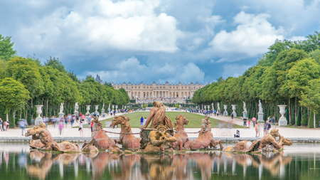 Apollo fountain in the Versailles Palace park timelapse, Ile de France. Royal Palace on background with reflection on water. Crowd of tourists at summer day